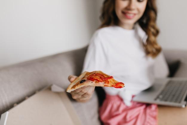 Mujer encantadora usando laptop y comiendo pizza con queso. filmación en interiores de chica relajada en camiseta blanca trabajando con computadora y disfrutando de comida rápida.