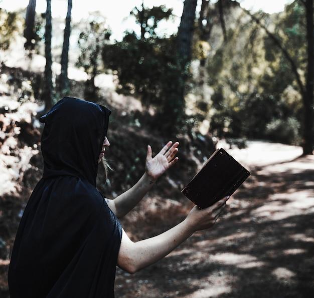Mujer encapuchada con libro conjurando en bosque iluminado por el sol