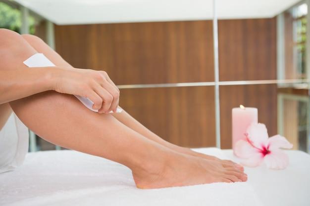 Mujer encerándose las piernas ella misma