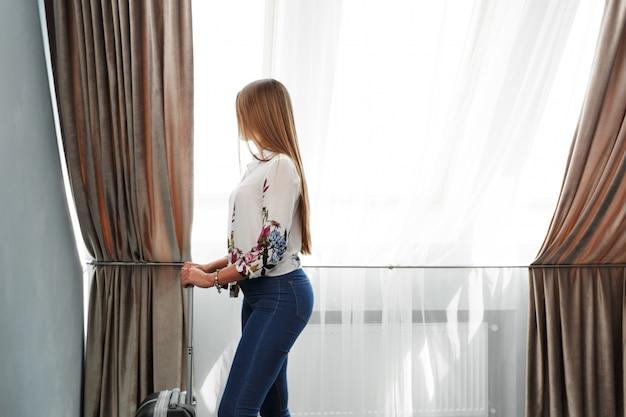 Mujer se encuentra cerca de la ventana en la habitación del hotel a la hora de la mañana