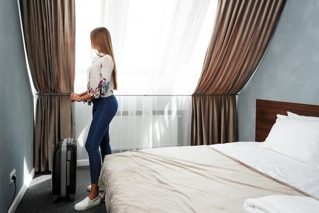 Mujer se encuentra cerca de la ventana en la habitación del hotel en el tiempo de la mañana