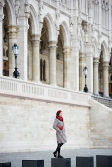 La mujer se encuentra en el contexto de una poderosa estructura arquitectónica europea.