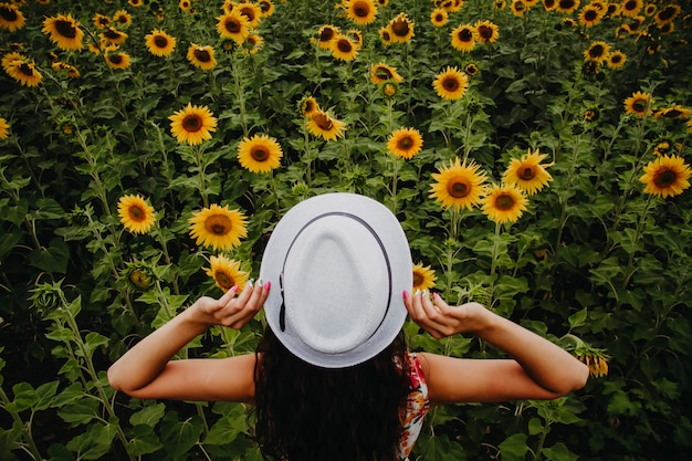 Una mujer se encuentra de espaldas al marco en un campo de girasoles sosteniendo su sombrero en sus manos.