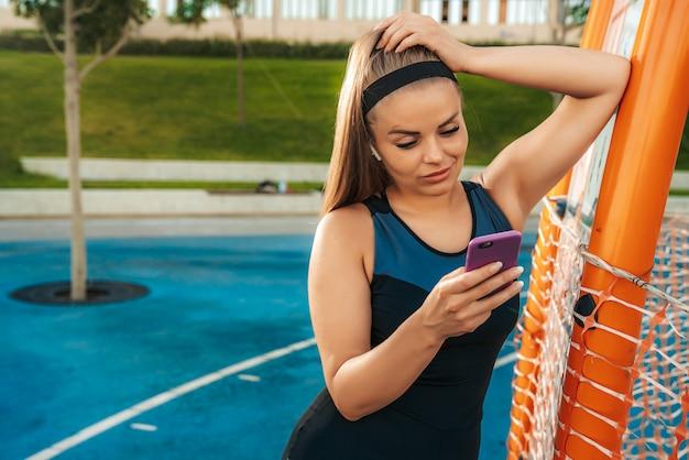 Una mujer se encuentra en el gimnasio al aire libre con un teléfono