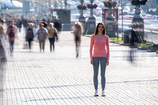 La mujer se encuentra en medio de una calle llena de gente.