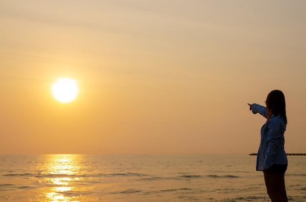 La mujer se encuentra en la puesta de sol sobre el mar y el cielo colorido.