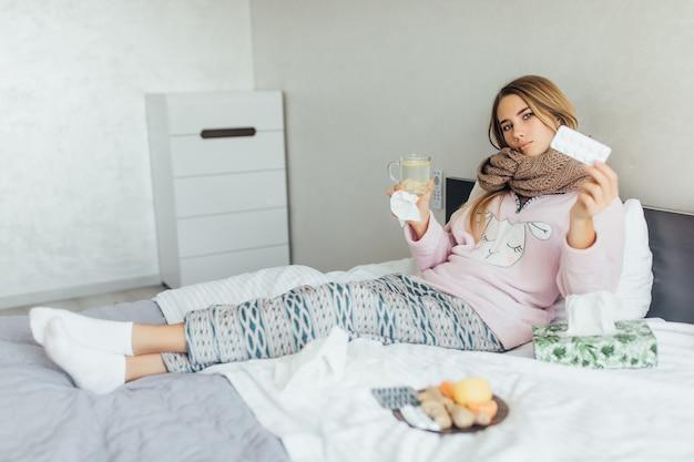 Mujer enferma acostada en la cama con fiebre alta