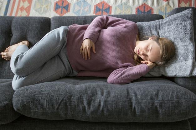 Mujer enferma acostada en el sofá gris en casa, sosteniendo la mano en el estómago
