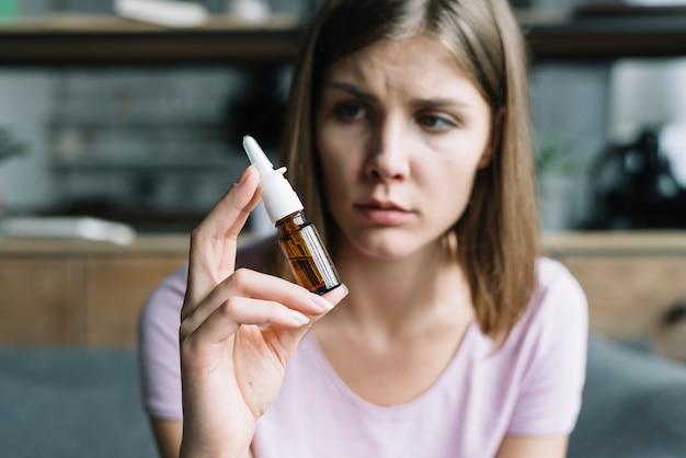 Mujer enferma con aerosol nasal en la mano