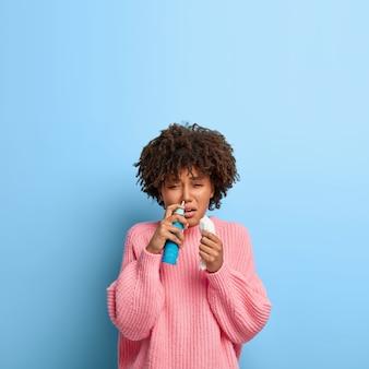 Mujer enferma con un afro posando en un suéter rosa