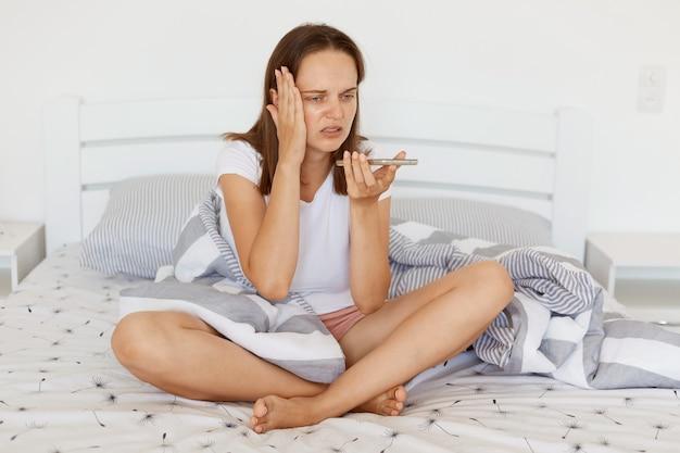 Mujer enferma con cabello oscuro con camiseta blanca casual posando en el dormitorio en la cama, grabando un mensaje de voz o comando a través de un teléfono inteligente, con dolor de cabeza, llamando a una ambulancia.