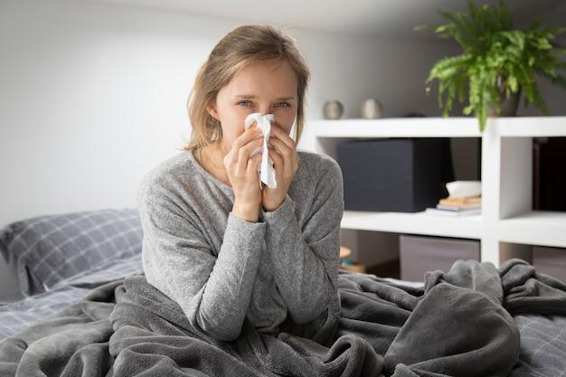 Mujer enferma en la cama que sopla la nariz con la servilleta, mirando a la cámara