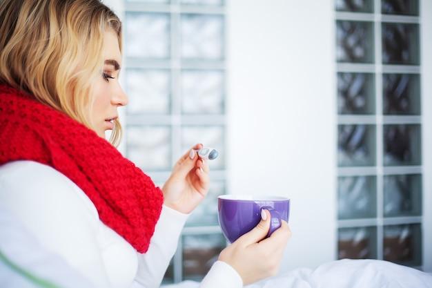 Mujer enferma en la cama con termómetro está teniendo fiebre alta temperatura