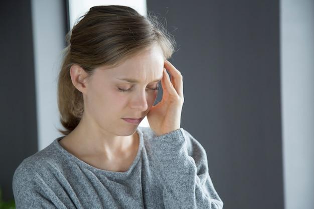 Mujer enferma en casa masajeando sien izquierda con mano