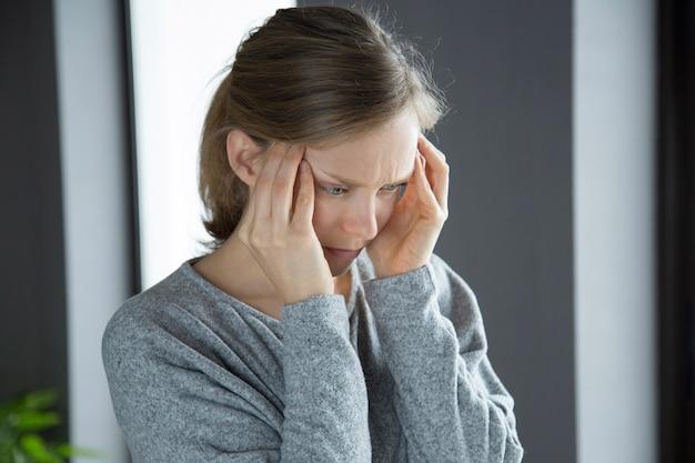 Mujer enferma en casa masajeando templos, sintiendo fuerte dolor de cabeza