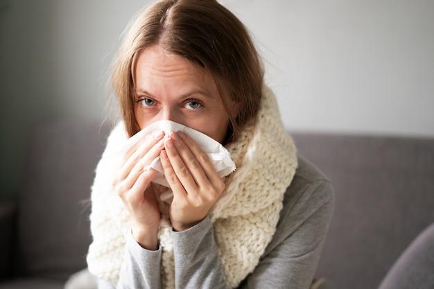 Una mujer está enferma en casa, secreción nasal y gripe.