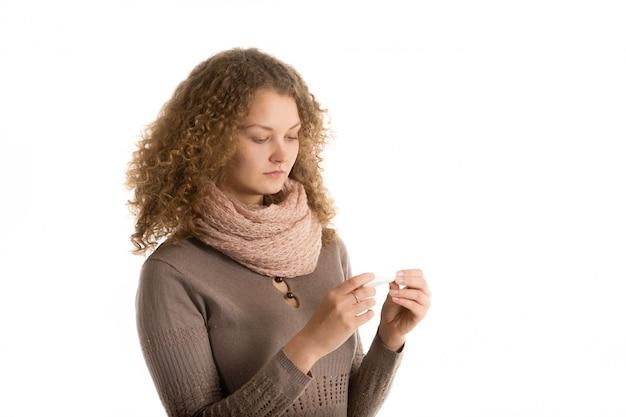 Mujer enferma comprobando el termómetro