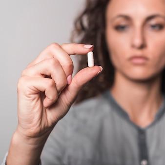 Mujer enferma con cápsula blanca en la mano