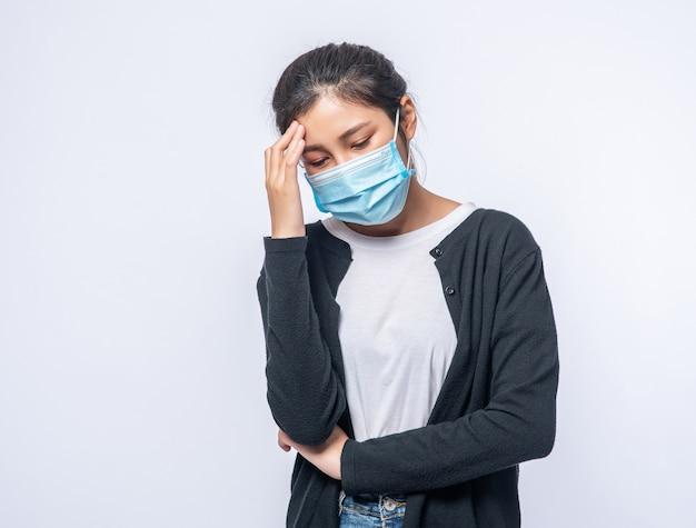 Una mujer enferma con dolor de cabeza se puso una máscara y se puso una mano en la cabeza.