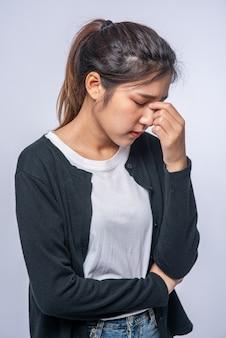 Una mujer enferma con dolor de cabeza y puso su mano sobre su cabeza.
