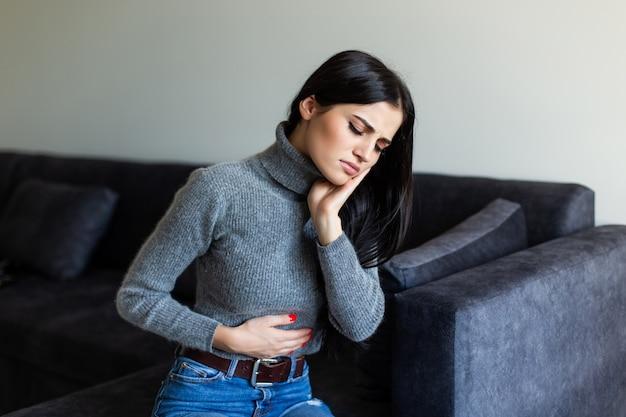Mujer enferma con dolor de estómago en la sala de estar