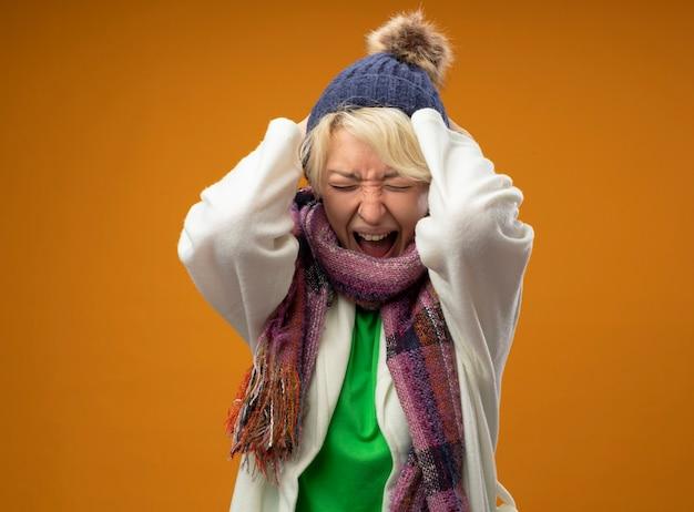 Mujer enferma enferma con pelo corto en bufanda caliente y sombrero gritando y gritando con expresión agresiva con las manos levantadas sobre fondo naranja