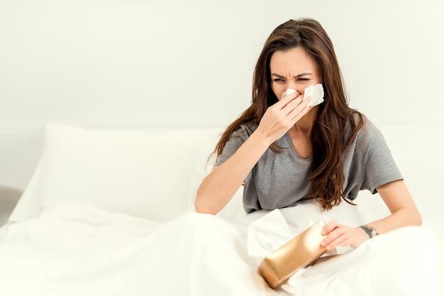 Mujer enferma y enferma que se despierta estornudando y usando pañuelos en la nariz.