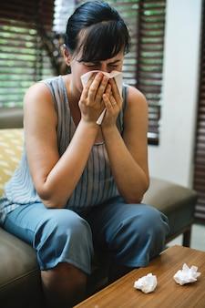 Mujer enferma estornudando en el tejido