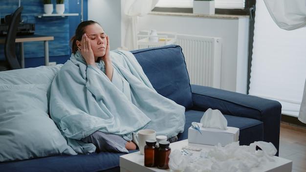 Mujer enferma frotándose las sienes y tratando de curar el dolor de cabeza