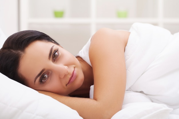 Mujer enferma gripe. chica con frío acostado debajo de una manta sosteniendo un pañuelo