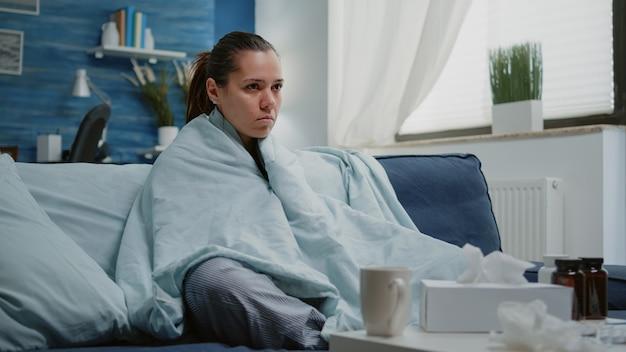Mujer enferma con gripe estacional temblando en una manta en casa