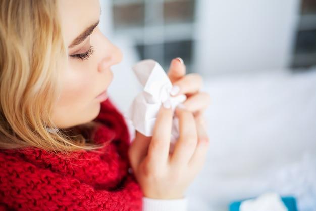 Mujer enferma con gripe. mujer que sufre de frío acostado en la cama con tejido