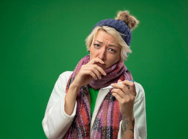 Mujer enferma insalubre con el pelo corto en bufanda caliente y sombrero sintiéndose mal sosteniendo el termómetro en la mano preocupado por sufrir de gripe y secreción nasal de pie sobre una pared verde