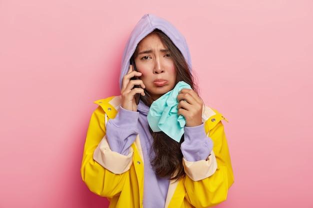Mujer enferma insatisfecha sostiene un pañuelo de papel, se resfría durante un paseo por la calle en un día lluvioso, le dice malas noticias a un amigo por teléfono celular, usa un impermeable amarillo necesita ver al médico