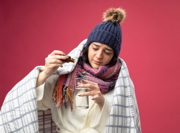 Mujer enferma joven concentrada con gorro de invierno bata y bufanda envuelta en cuadros agregando medicamento en un vaso de agua aislado en la pared rosa