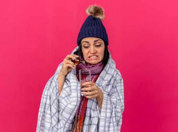 Mujer enferma joven concentrada con gorro de invierno y bufanda envuelta en cuadros añadiendo medicamento en un vaso de agua aislado en la pared rosa