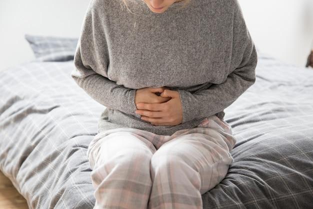 Mujer enferma con las manos en el estómago sufriendo de intenso dolor.