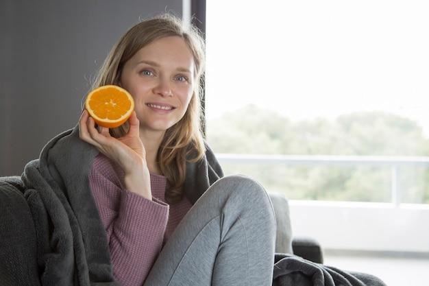 Mujer enferma mirando a cámara, mostrando la mitad de naranja, sonriendo