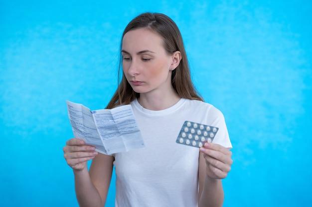 Mujer enferma mirando la explicación del medicamento antes de tomar medicamentos recetados