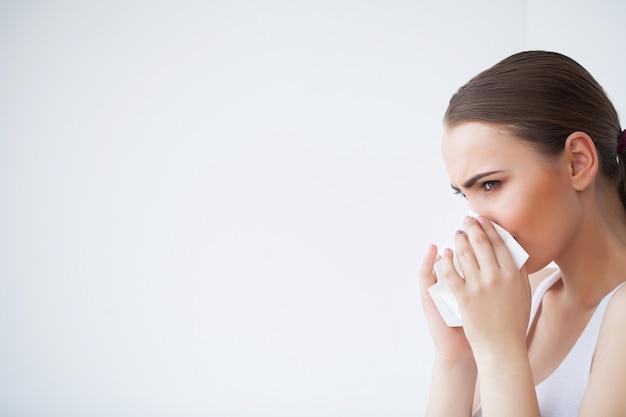 Mujer enferma con pañuelos de papel, problema de cabeza