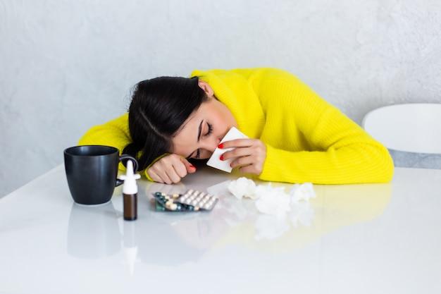 Mujer enferma con pastillas en la mesa de la cocina