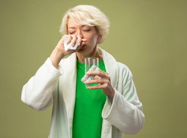 Mujer enferma con el pelo corto que se siente mal sosteniendo un vaso de agua y una ampolla con pastillas limpiando su nariz con una servilleta de pie sobre un fondo claro
