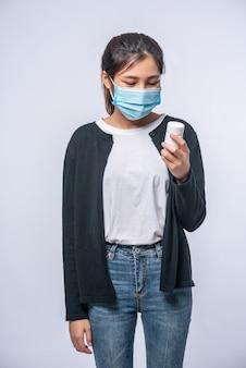 Una mujer enferma de pie con un frasco de medicina.