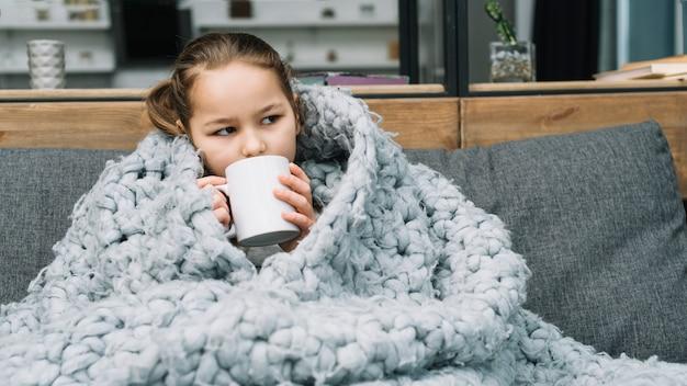 Mujer enferma que cubre bufanda de lana alrededor de ella tomando café de la taza