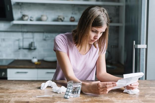 Mujer enferma que mira la prescripción con el paquete de ampolla y el vidrio de agua en el escritorio de madera