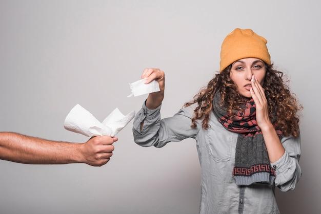 Mujer enferma que sufre de frío tomando papel de seda de la mano del hombre