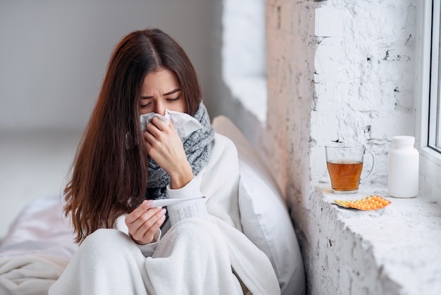 Mujer enferma resfriada, sintiendo enfermedad y estornudando con papel
