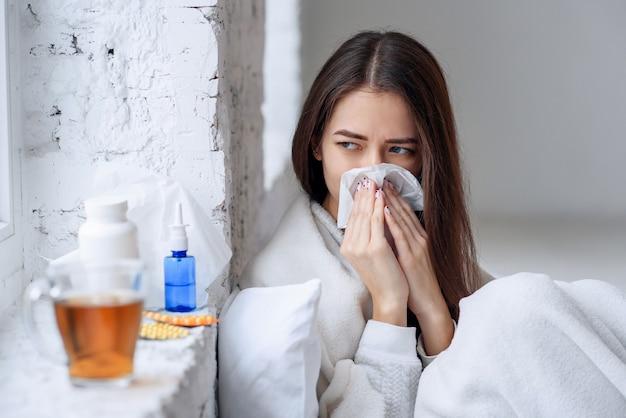 Mujer enferma resfriada, sintiéndose enferma y estornudando en papel