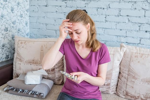 Una mujer enferma con un resfriado mira las pastillas. fiebre alta y dolor de cabeza por gripe y enfermedades virales. tratamiento a domicilio. volgodonsk, rusia 04 de mayo de 2019