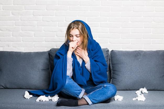Mujer enferma con reum y dolor de cabeza sosteniendo una servilleta, sentada en el sofá con colcha y pastillas en casa